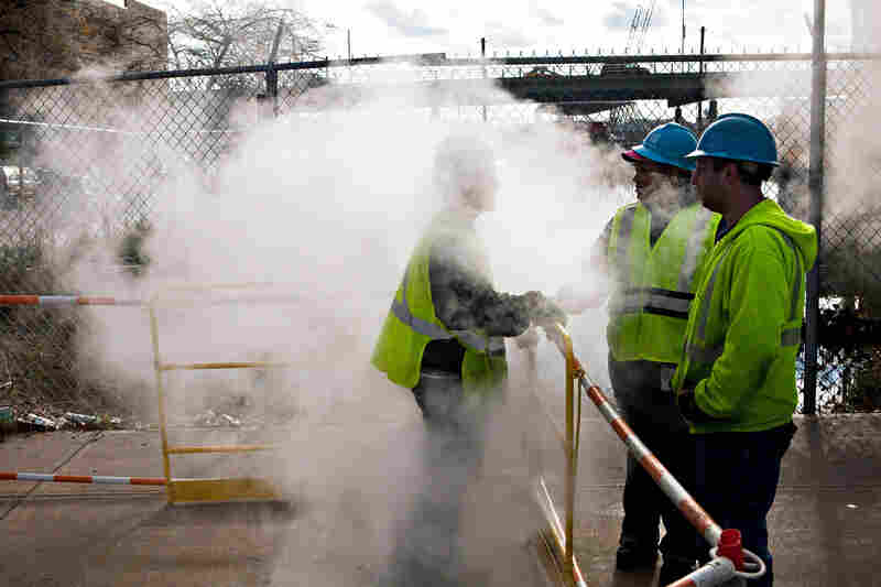 Con Edison employees work on a steam pipe on First Avenue in New York City. Businesses across the Eastern Seaboard are attempting to return to normal as cleanup continues.