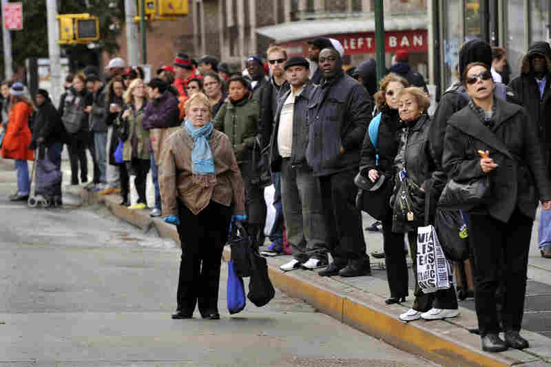 People wait for buses on 6th Avenue in New York City. The crippled subway system, traffic-clogged roads and large areas still without power pose a daunting hurdle as New Yorkers cope with Sandy's aftermath.