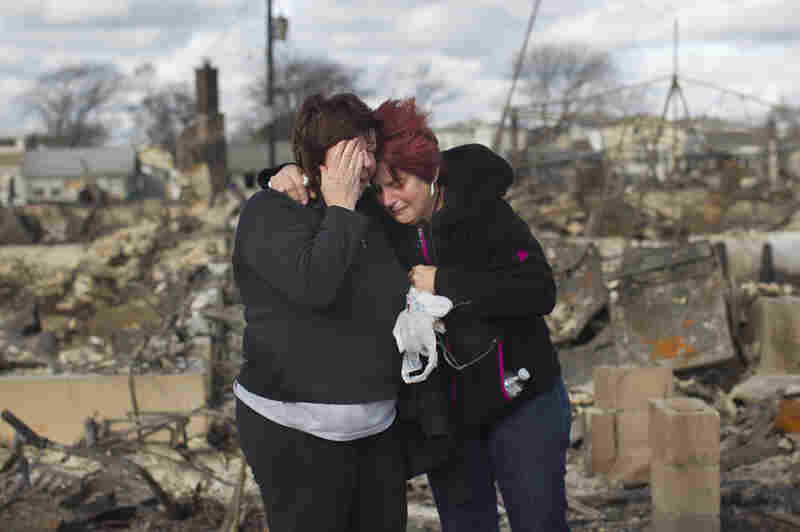 Neighbors Lucille Dwyer (right) and Linda Strong embrace after looking through the wreckage of their homes, which were devastated by fire and the storm in the Breezy Point neighborhood of Queens, N.Y.