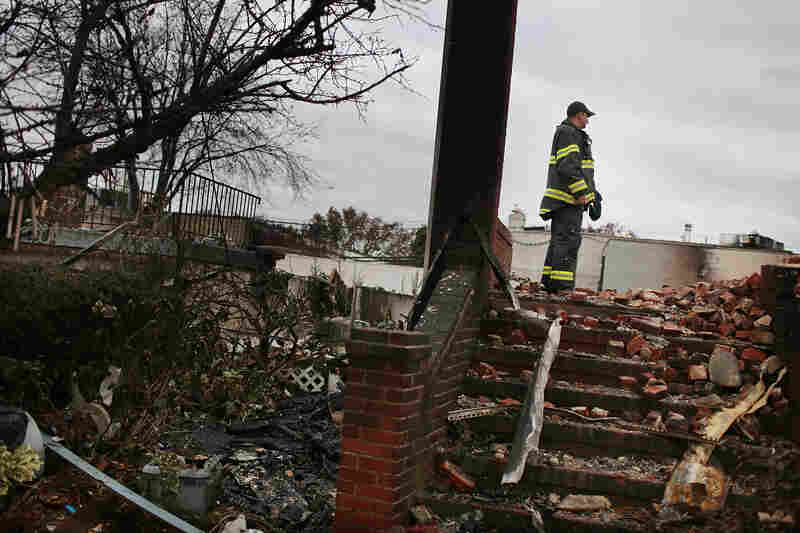 A firefighter stands in the remains of a home destroyed by fire in the Rockaway neighborhood of Brooklyn, N.Y.