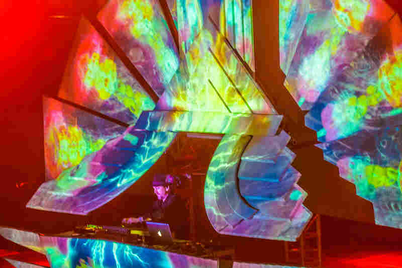 The English psych-ambient performer Shpongle performs at a sort of rainbow-colored throne.