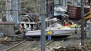 Workers try to clear boats and debris from the New Jersey Transit's Morgan draw bridge on Wednesday in South Amboy, N.J., after Monday's storm surge from Sandy pushed boats and cargo containers onto the train tracks.