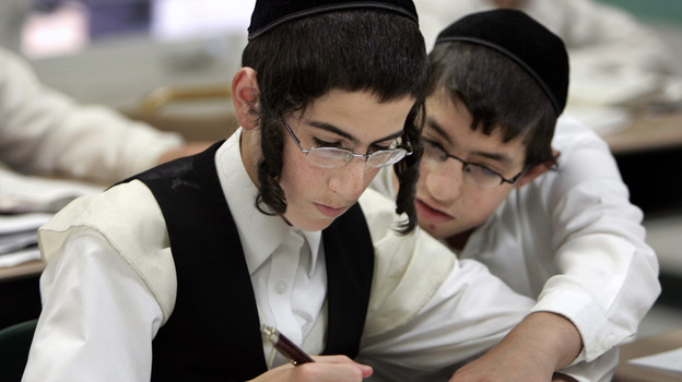 Two boys study together at a Chicago yeshiva in 2009. Public health officials say this type of close physical contact caused a mumps outbreak to spread throughout several orthodox Jewish communities in and around New York City. (AP)