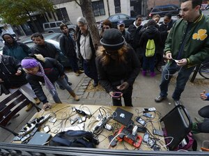 People wait to charge cellphones and laptops Thursday at a generator set up in the West Village. Superstorm Sandy left lar
