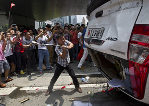 As part of a demonstration against Japan, a Chinese protester destroys a Japanese-model police car in Shenzhen, in southern China on Aug. 19, 2012.