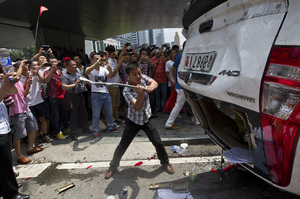 As part of a demonstration against Japan, a Chinese protester destroys a Japanese-model police car in Shenzhen in southern China on Aug. 19.