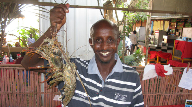Somali chef Ahmed Jama holds up freshly caught spiny lobsters he's about to cook in one of his restaurants in Mogadishu. (NPR)