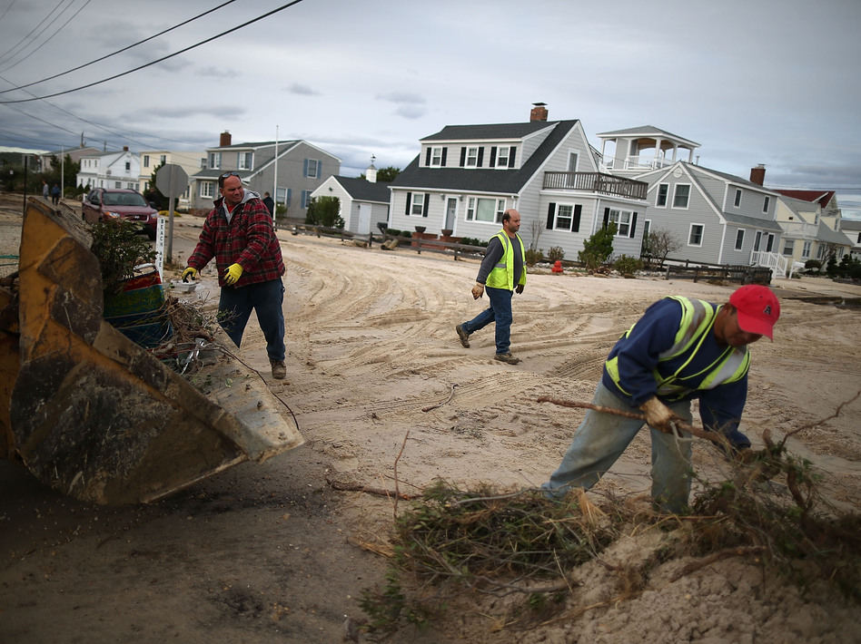 Workers clean up debris left by Superstorm Sandy in Long Beach Island, N.J., on Wednesday. The storm may lead to layoffs as business losses mount, but also could result in hiring related to rebuilding.