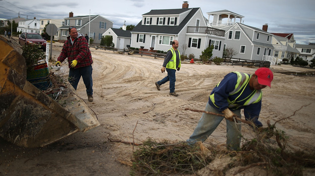 Workers clean up debris left by Superstorm Sandy in Long Beach Island, N.J., on Wednesday. The storm may lead to layoffs as business losses mount, but also could result in hiring related to rebuilding. (Getty Images)