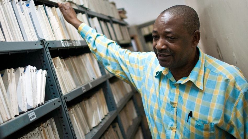 Radio Tanzania archivist Bruno Nanguka stands with just a few of the 15,000 reel-to-reel tapes stored in the station's archives. (Jonathan Kalan)