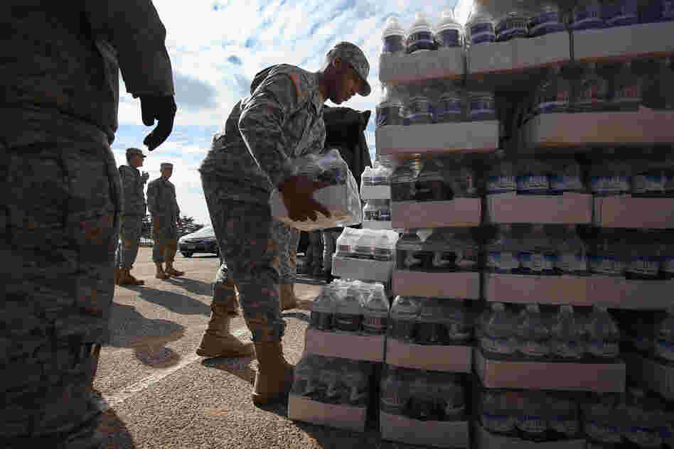 New York National Guard troops unload water to distribute to residents.