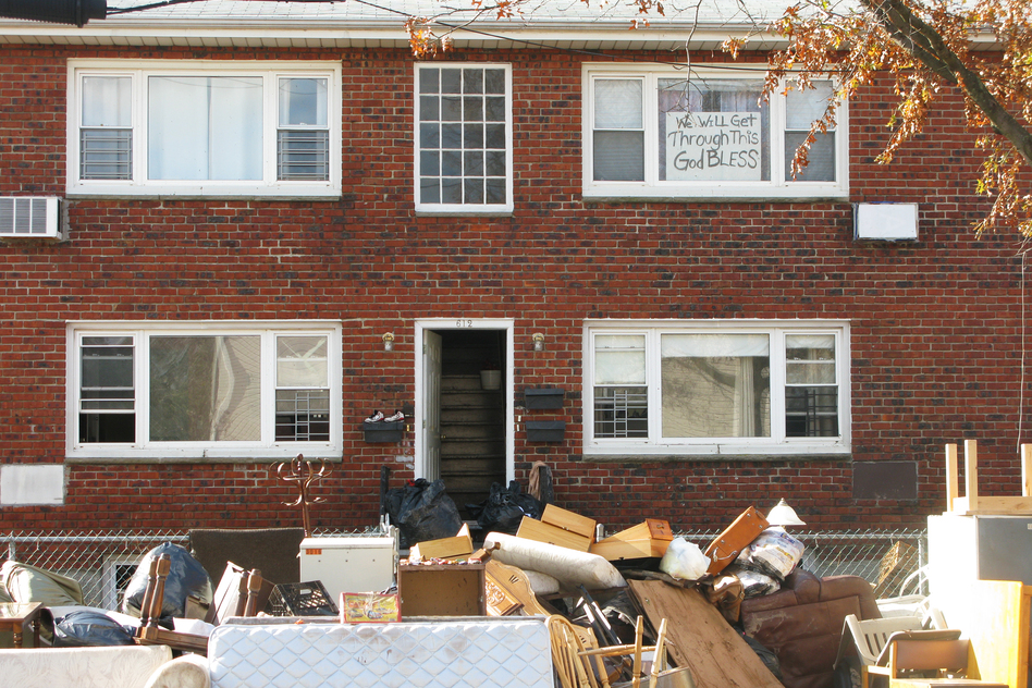 "An apartment building's contents are placed on the sidewalk during cleanup from Superstorm Sandy. The sign in the window reads, ""We will get through this. God bless."""