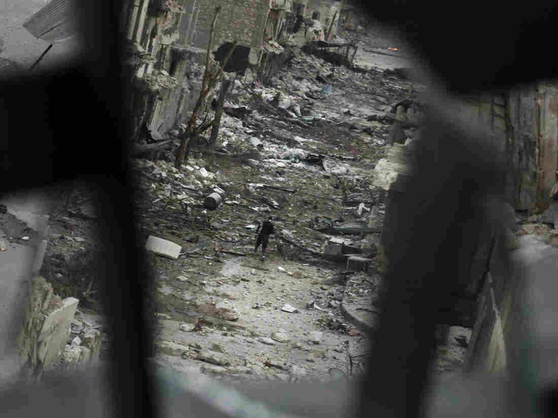 In Aleppo, Syria, this week: A rebel crossed a ruined street. This image shows him in a mirror's reflection.
