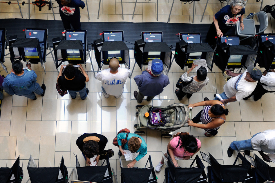 Voters cast their ballots during the first day of early voting at the Meadows Mall on Oct. 20 in Las Vegas, Nev.