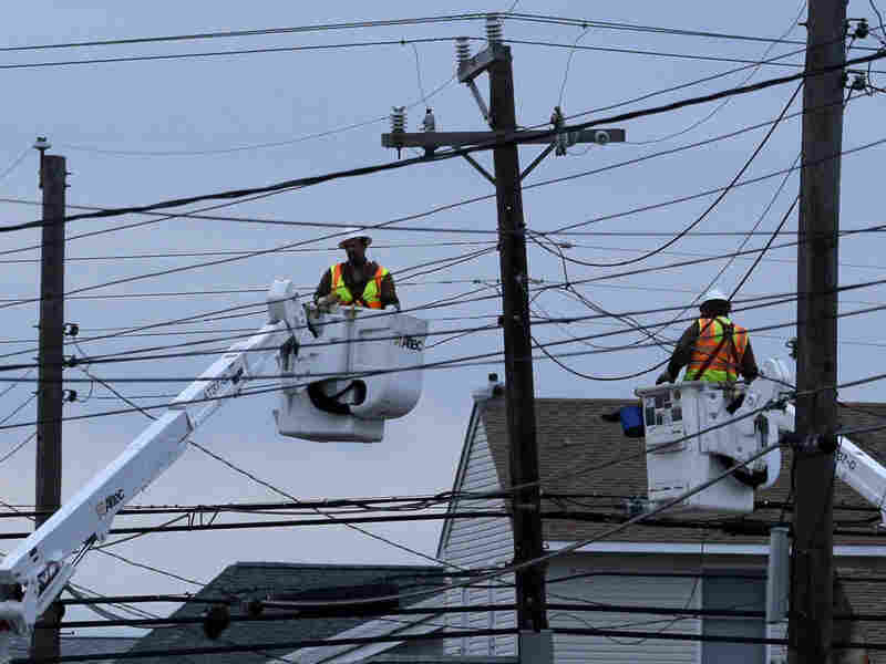 Utility crews work on power lines as dusk falls in Ship Bottom, a community on Long Beach Island, N.J.