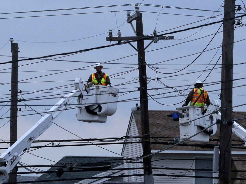 Utility crews work on power lines in response to Superstorm Sandy as dusk falls in Ship Bottom, a community on Long Beach Island, N.J. There are 2.5 million people across N.J. still waiting for power.