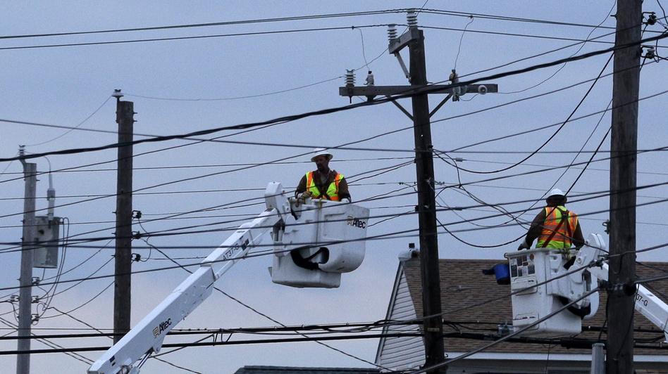 Utility crews work on power lines as dusk falls in Ship Bottom, a community on Long Beach Island, N.J. (AP)