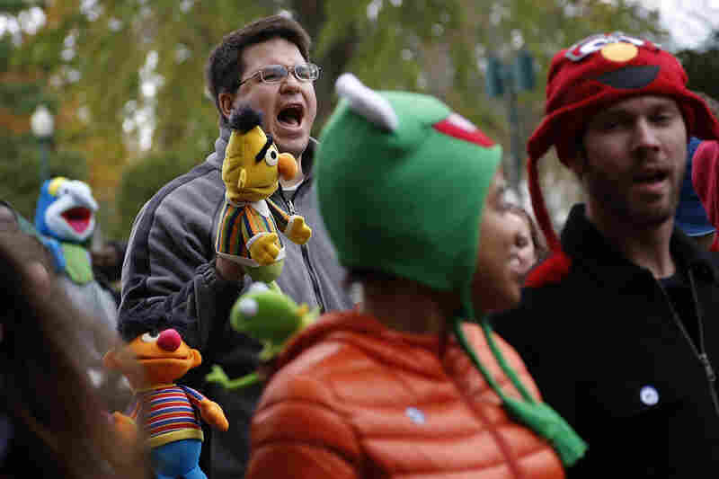 A demonstrator with a puppet of Bert, the Muppet character from Sesame Street, shouts during The Million Muppet March in Washington, D.C., on Saturday. The bipartisan rally was organized to show support for public broadcasting following Republican presidential candidate Mitt Romney's pledge to cut funding to PBS.
