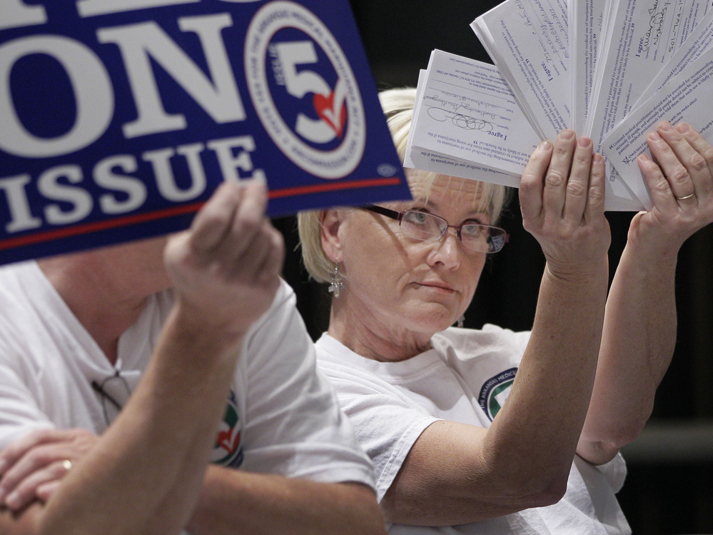 Melissa Fults, treasurer for Arkansans for Compassionate Care, holds up cards at the back of a news conference in Little Rock, Ark., with the names of doctors she says support a ballot issue that would legalize medical marijuana.