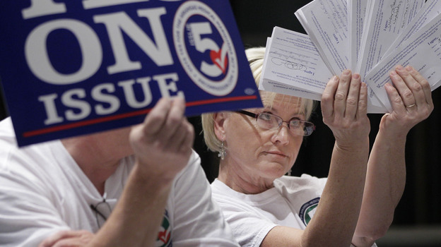 Melissa Fults, treasurer for Arkansans for Compassionate Care, holds up cards at the back of a news conference in Little Rock, Ark., with the names of doctors she says support a ballot issue that would legalize medical marijuana. (AP)