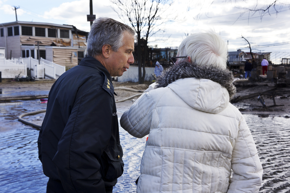 New York Fire Department Chief Joseph Pfeifer consoles a woman who lost her home. The small seaside community lost 111 homes as fires raged in the 50-mph winds of Superstorm Sandy. (NPR)