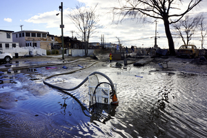"""Firefighters are part of a massive de-watering effort in Breezy Point. """"We're trying to put the water back where it came from,"""" says Chief Pfeifer."""