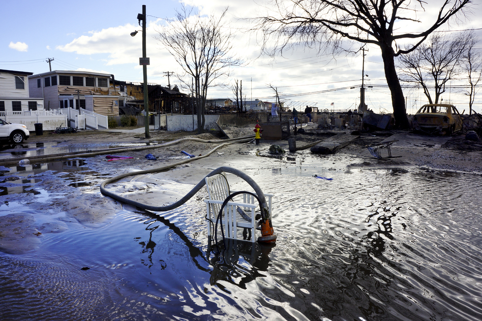 "Firefighters are part of a massive de-watering effort in Breezy Point. ""We're trying to put the water back where it came from,"" says Chief Pfeifer. (NPR)"