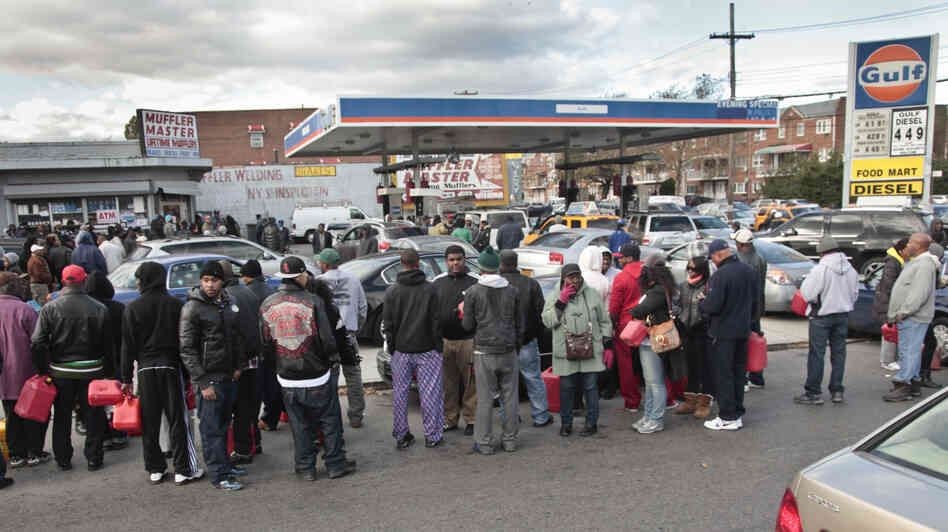 Gas customers on foot with portable containers and lines of vehicles wait for gas pumps to open at a service station on Saturday in the Brooklyn borough of New York. Mayor Michael Bloomberg said that resolving gas shortages could take days.