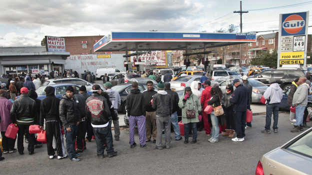 Gas customers on foot with portable containers and lines of vehicles wait for gas pumps to open at a service station on Saturday in the Brooklyn borough of New York. Mayor Michael Bloomberg said that resolving gas shortages could take days. (AP)