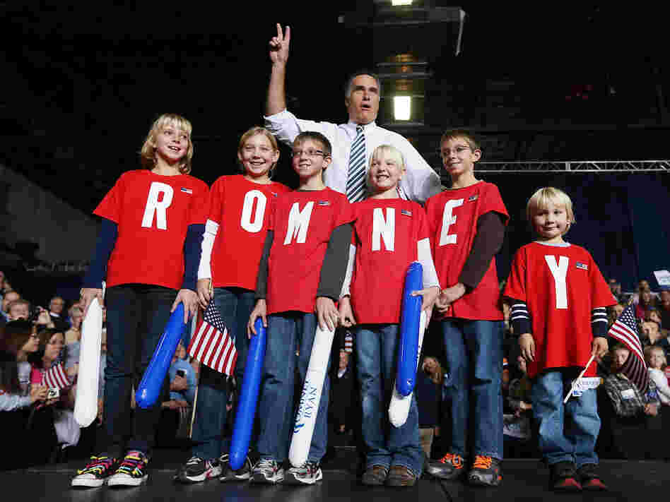 Republican presidential candidate Mitt Romney poses with children during a campaign rally in Des Moines, Iowa, on Sunday.