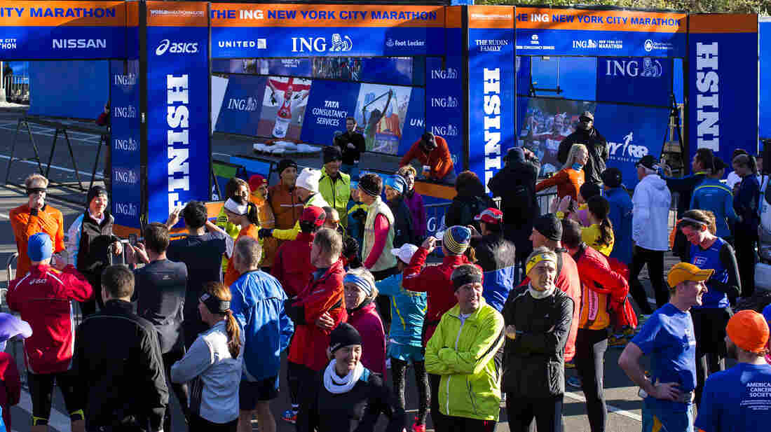 A crowd of runners stands near the barricaded Central Park finish line for the now-canceled New York Marathon on Saturday.