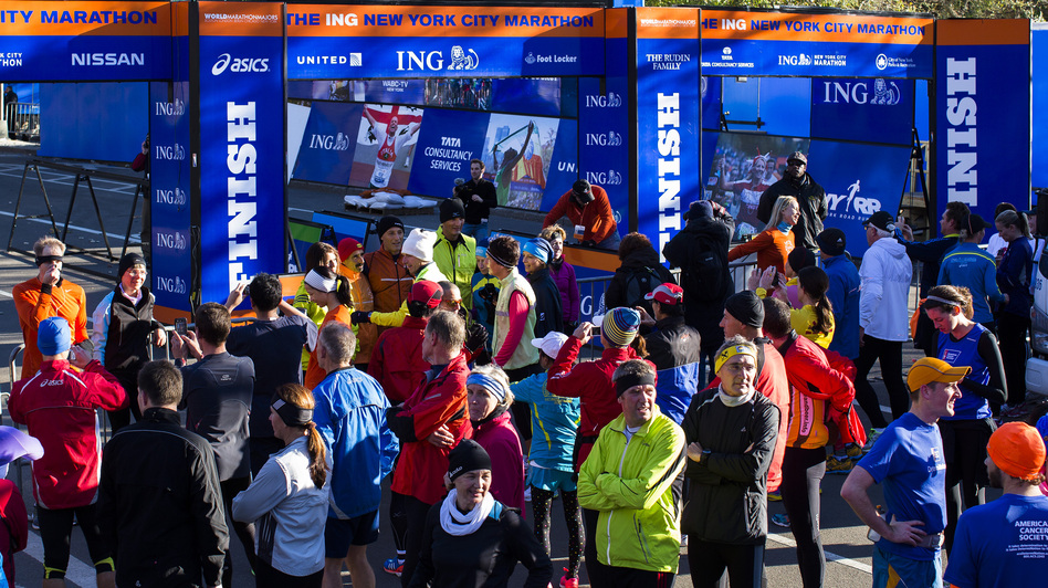 A crowd of runners stands near the barricaded Central Park finish line for the now-canceled New York Marathon on Saturday. (AP)