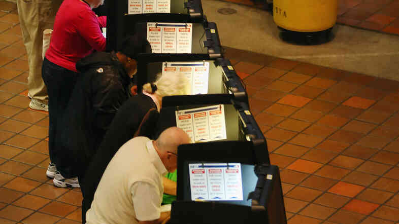 Voters fill out their ballots on the first day of early voting on Oct. 27 in Miami.