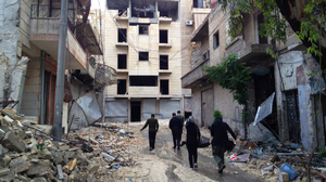 In one Aleppo neighborhood, government forces and rebel fighters are separated by an abandoned building that forms the front line. Most civilians have fled, and rebels live in the abandoned apartments. Government snipers are posted on rooftops.