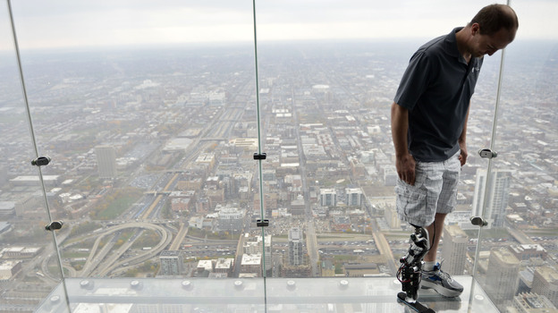 """Zac Vawter, fitted with an experimental """"bionic"""" leg, looks down from the Ledge at the Willis Tower, on Thursday in Chicago. (AP)"""