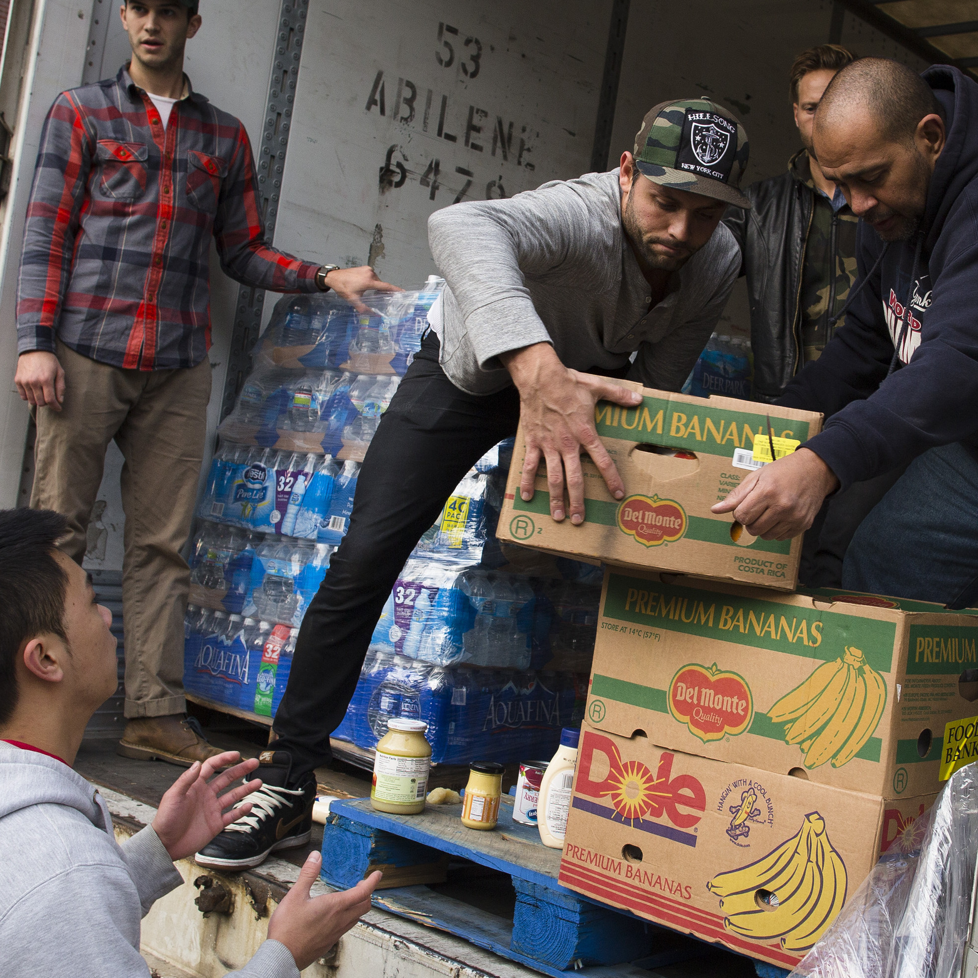 Volunteers help unload food to distribute to residents of the Lower East Side who remain without power due to Superstorm Sandy on Friday. Some got fresh foods but many got ready to eat meals.