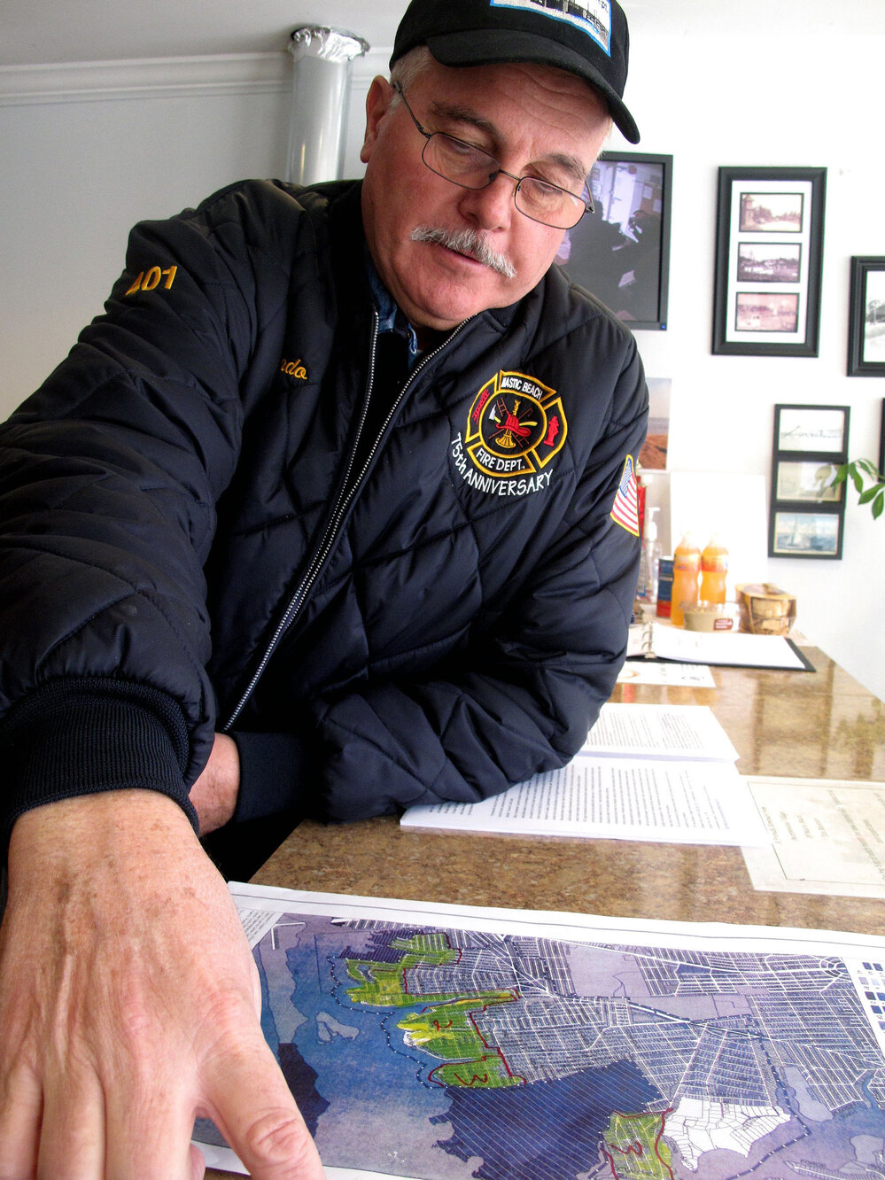 Mastic Beach Mayor Bill Biondi looks over a map of the flooding in his community from Hurricane Sandy. More than a thousand homes here were inundated with seawater.