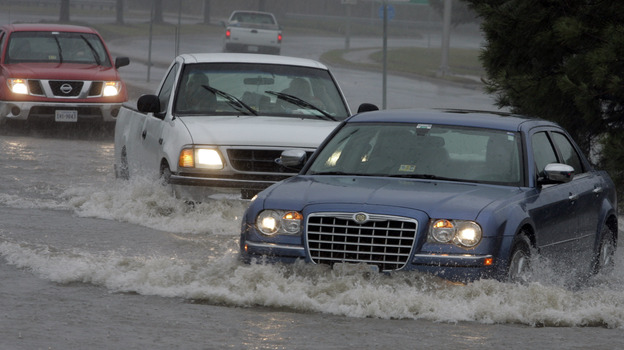 Motorists drive through standing water at an intersection flooded from the remnants of Tropical Storm Ida in the Ocean View area of Norfolk, Va., in November 2009. (AP)