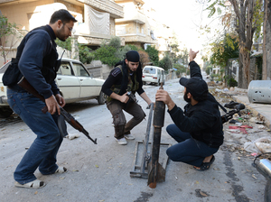 Syrian rebel fighters prepare to launch a rocket in the northern city of Aleppo on Saturday. The rebels say they have launched a major assault on a government air base in northern Syria.