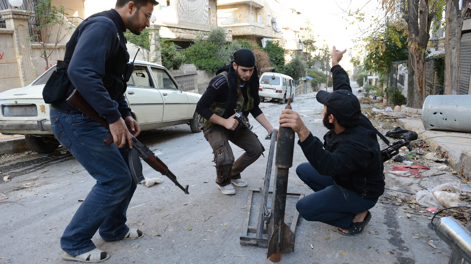 Syrian rebel fighters prepare to launch a rocket in the northern city of Aleppo on Saturday. The rebels say they have launched a major assault on a government air base in northern Syria. (AFP/Getty Images)