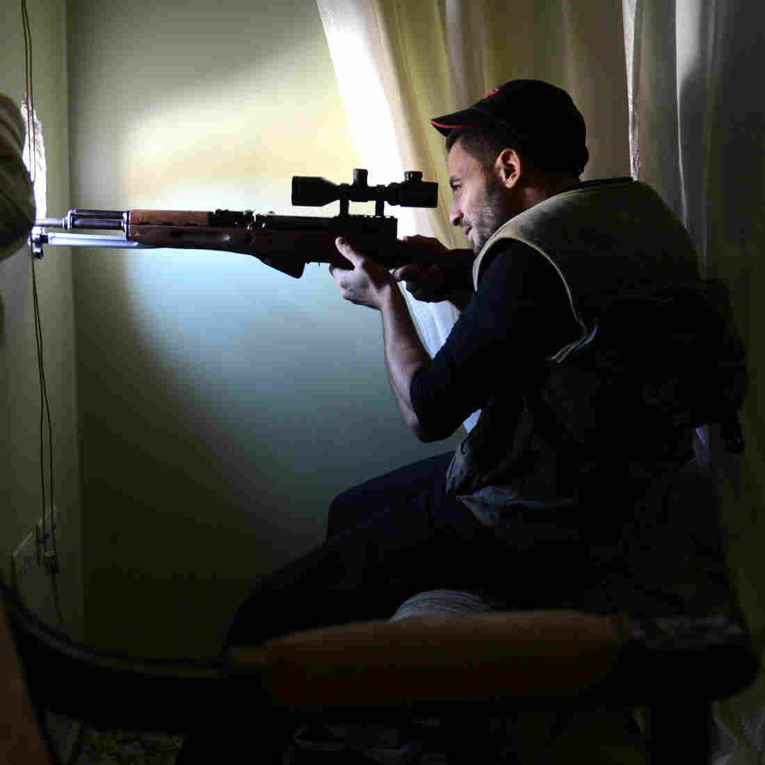 A Syrian rebel fighter takes aim at government forces from an apartment in the northern city of Aleppo on Saturday. While the fighting rages, the Syrian opposition is holding talks in Qatar in an attempt to create a new, more unified front. The U.S. announced last week that it favors an overhaul of the opposition leadership.