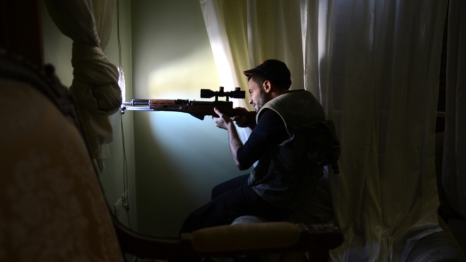 A Syrian rebel fighter takes aim at government forces from an apartment in the northern city of Aleppo on Saturday. While the fighting rages, the Syrian opposition is holding talks in Qatar in an attempt to create a new, more unified front. The U.S. announced last week that it favors an overhaul of the opposition leadership. (AFP/Getty Images)