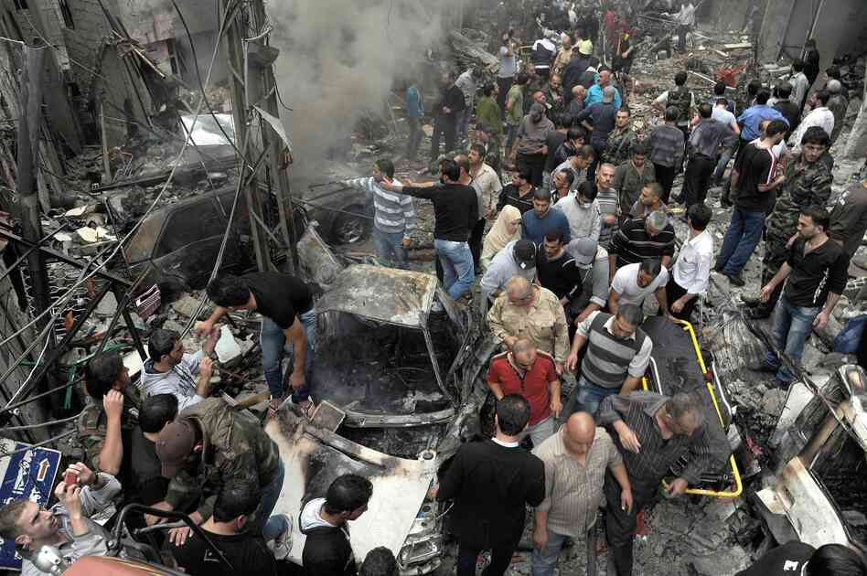 Syrians gather at the site of a car bombing Monday that killed 11 people and wounded dozens in Damascus,