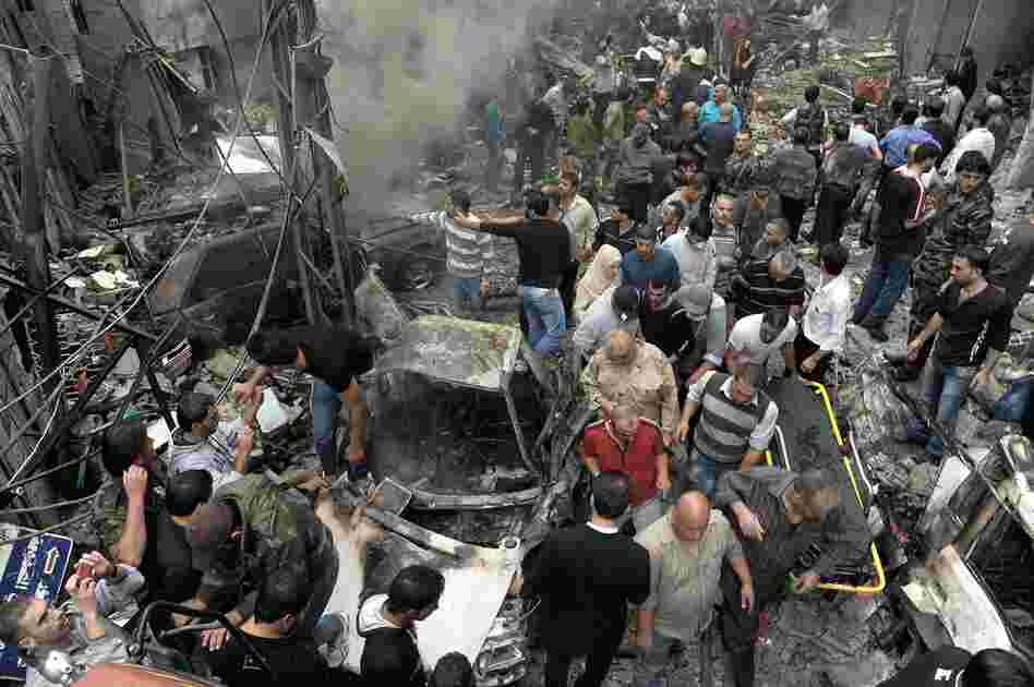 Syrians gather at the site of a car bombing Monday that killed 11 people and wounded dozens in the capital Damascus, according to the SANA news agency, which provided the photo. The violence in the city was described as some of the worst in recent months.