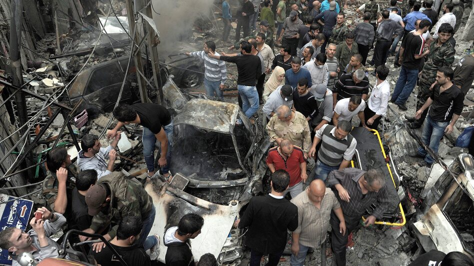 Syrians gather at the site of a car bombing Monday that killed 11 people and wounded dozens in Damascus, according to the SANA news agency, which provided the photo. The violence in the city was described as some of the worst in recent months. (EPA/Landov)