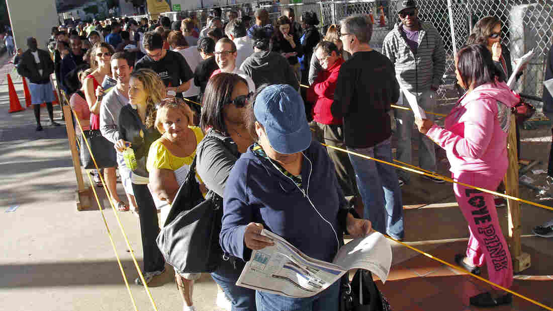 Floridians stand in line during the last day of early voting in Miami on Saturday. A judge extended early-voting hours in one Florida county Sunday after Democrats sued to allow more time.