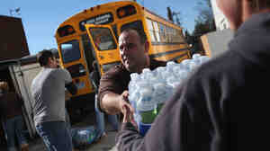 Long Beach, N.Y.: Volunteers unloaded water at an aid distribution center on Sunday.