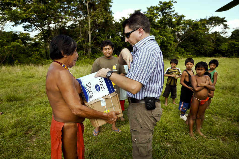 In French Guiana, ballot materials are taken to the territory's most isolated villages by helicopter. French civil servant Patrick Arnaud (center) delivers parcels in the village of Trois Sauts in 2012, for the second round of the French parliamentary election.