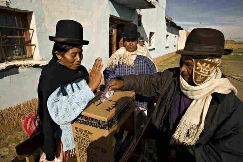 In Bolivia, a voter casts a ballot on a referendum for a new constitution in the rural town of Chipamaya outside La Paz in 2009.