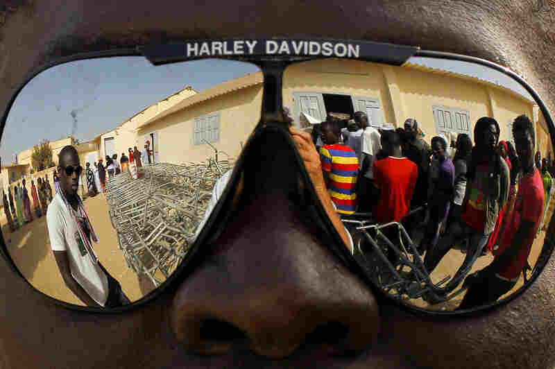 Voters in Senegal, reflected in a pair of sunglasses, wait to cast ballots in the presidential election in Senegal, 2012.